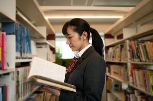 図書室で本を読む女子高校生の写真素材 [FYI01220978]