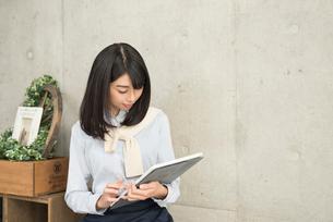 iPadを使っている20代OL女性の写真素材 [FYI01221394]