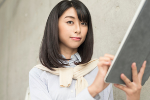 iPadを手に持って指で操作する20代OL女性カメラ目線 FYI01221396