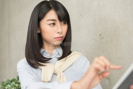 iPadを指で操作する20代OL女性 FYI01221397
