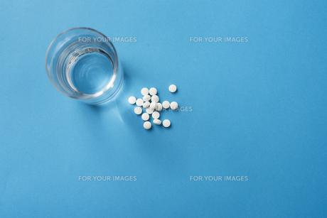 水の入ったコップと白い錠剤の写真素材 [FYI01222218]