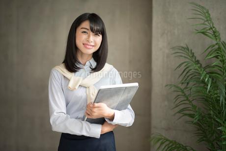 iPadを両手で抱えて笑う20代OL女性の写真素材 [FYI01224953]