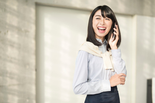 iPhoneで通話中に口を大きく開けて笑う20代OL女性。顔寄り。目線外し。の写真素材 [FYI01225176]