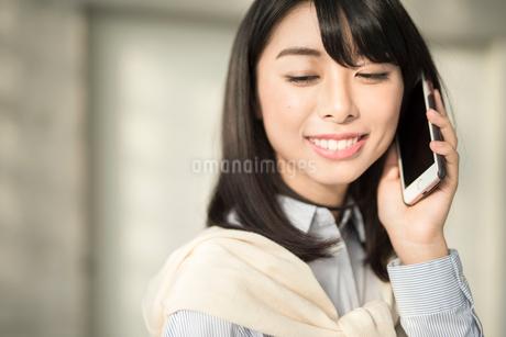 iPhoneで通話中の笑顔な20代OL女性。顔寄り。目線外し。の写真素材 [FYI01225178]