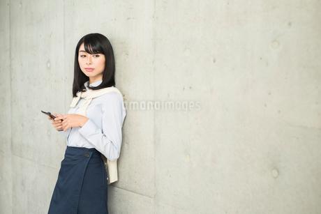 iPhoneを操作している女性。目線外し。の写真素材 [FYI01226702]