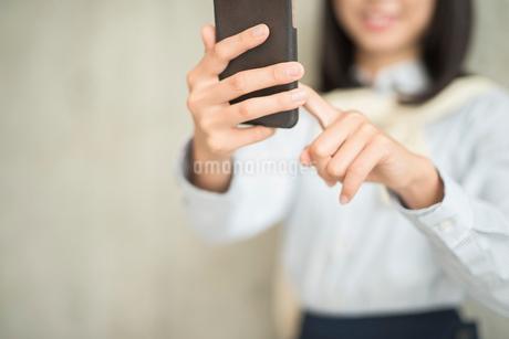 iPhoneを操作している笑顔の女性の手元の寄り。指差し。の写真素材 [FYI01226706]