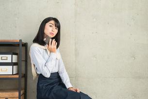 iPhoneを顎に当て首をかしげる20代OL女性の写真素材 [FYI01227303]